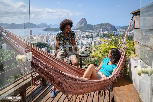 Brazilian couple smiling at each other on decking, woman in hammock, Sugar Loaf Mountain in the distance