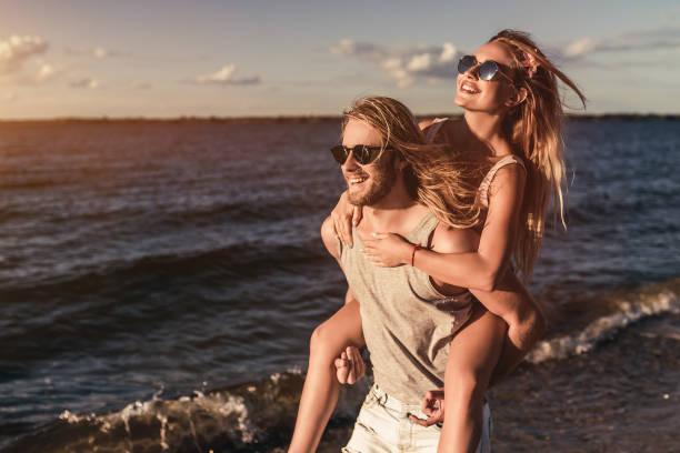 young couple on beach - spiaggia coppia amore foto e immagini stock
