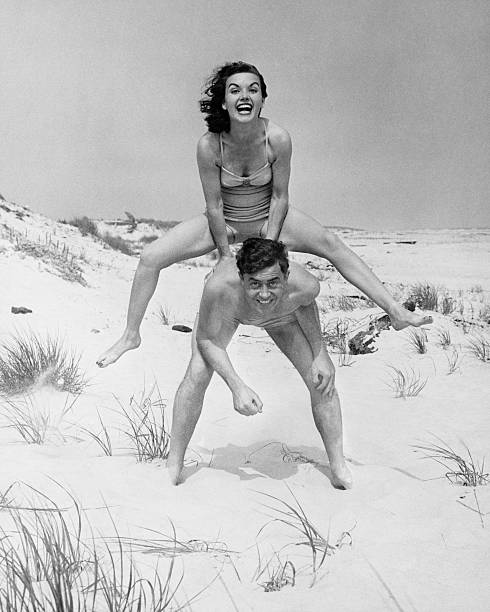 Young couple on beach, woman leap-frogging man, (B&W), portrait stock photo