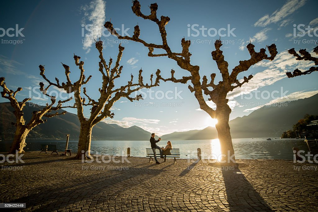 Young couple on bench at sunset taking picture with phone stock photo