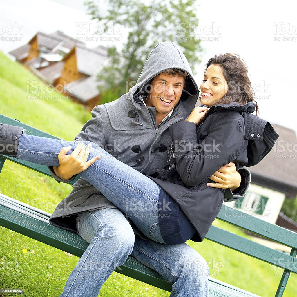 young couple on bench laughing royalty-free stock photo