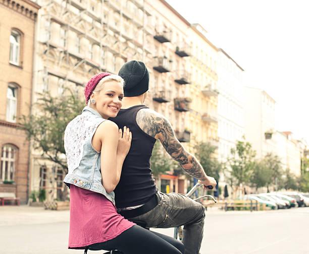 junges paar auf fahrrädern - ehepaar tattoos stock-fotos und bilder