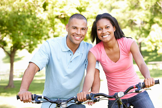 Young couple on bicycles posing and smiling in a park stock photo