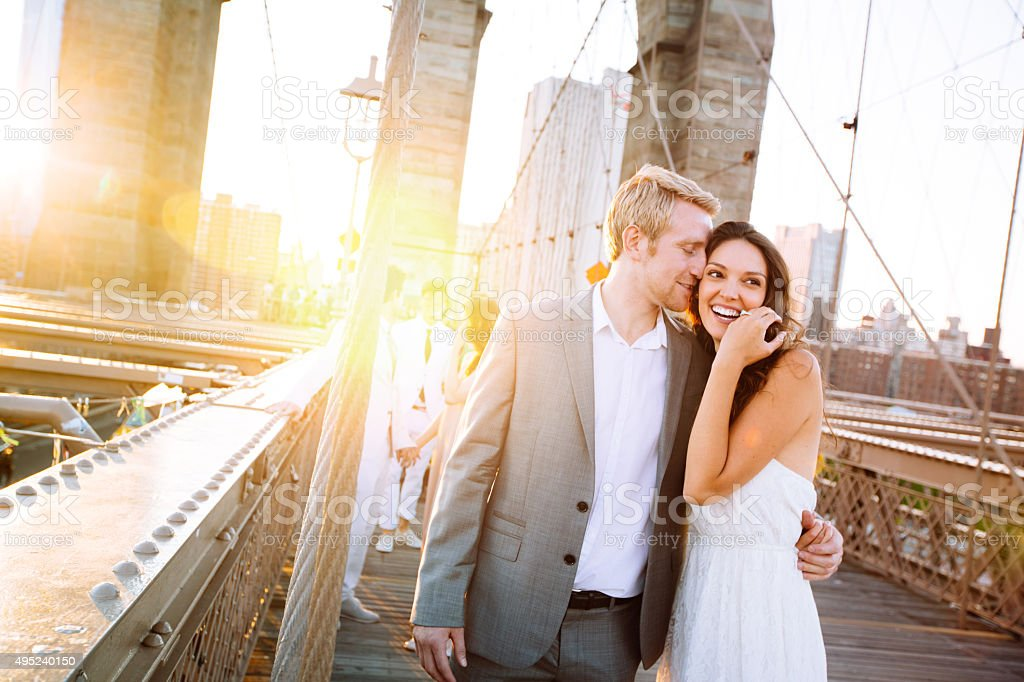 Young couple on Brooklyn Bridge at sunset stock photo