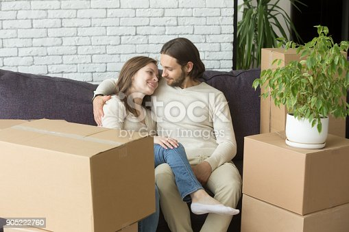 938682826istockphoto Young couple on couch moved in new home with boxes 905222760