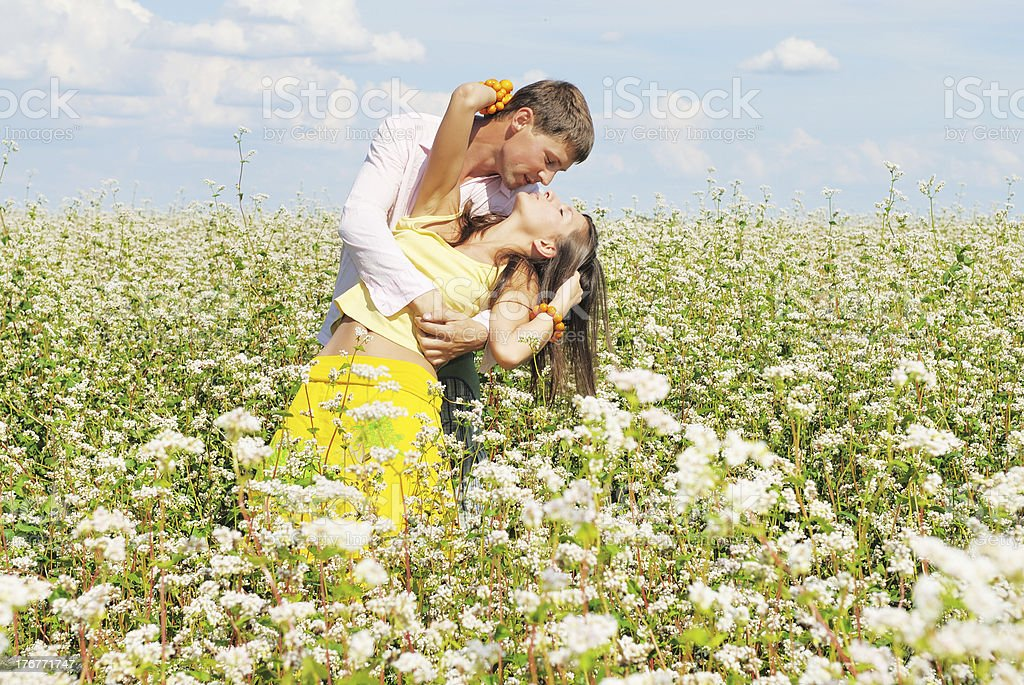Young couple on field of flowers royalty-free stock photo