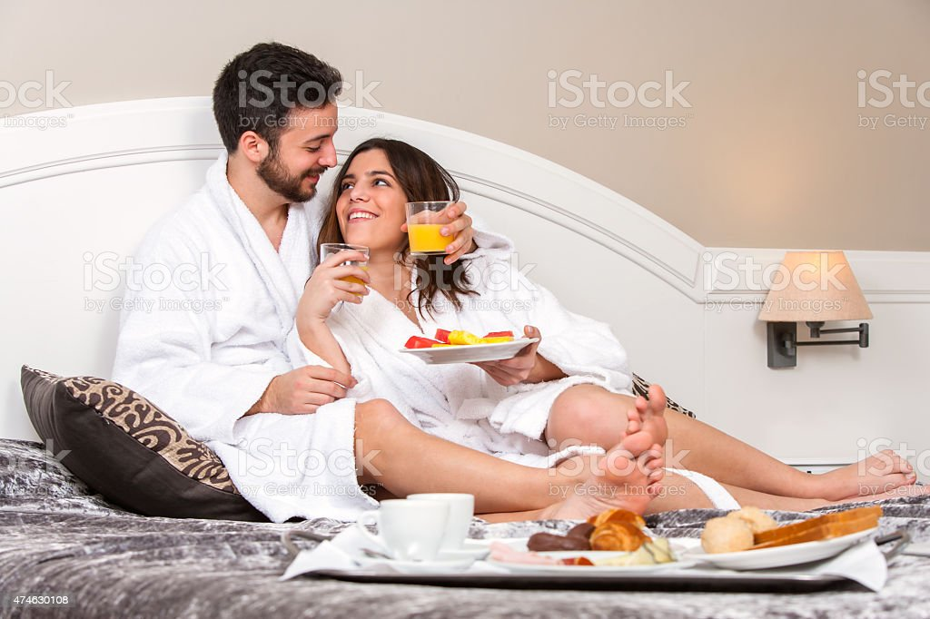 Young couple on honeymoon in hotel room. stock photo