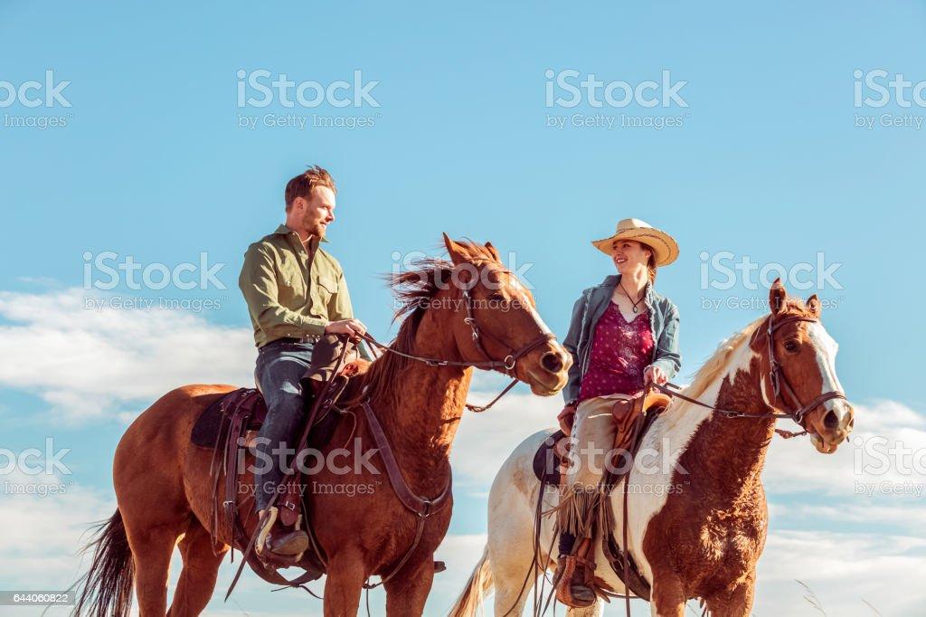 Young Couple On Horseback Outdoors stock photo