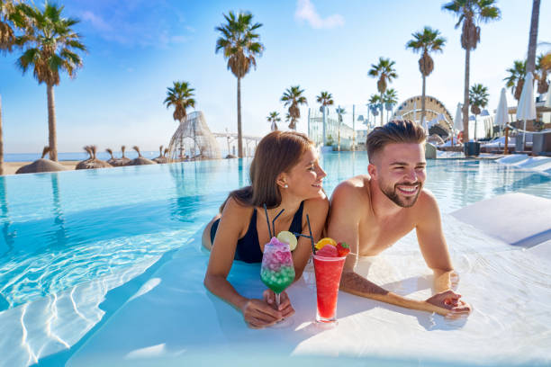 Young couple on infinity pool cocktails stock photo