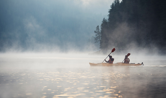 Young couple on kayaking adventure in mountain lake.