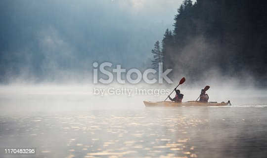 Couple rowing kayak in beautiful mountain lake at twilight, floating on water with mistycal mood.