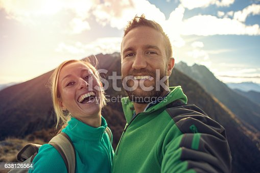 istock Young couple on mountain top take selfie portrait 638126564