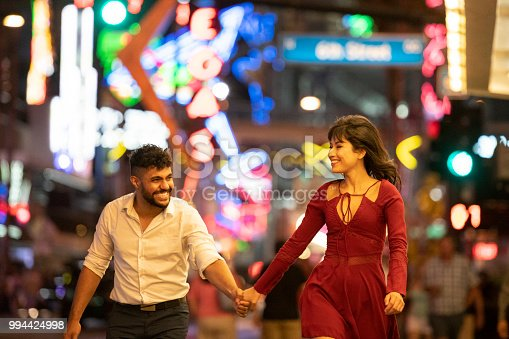 Multi ethnic man and woman in their 20's, having fun flirting and laughing together in the city at night with bright background lights