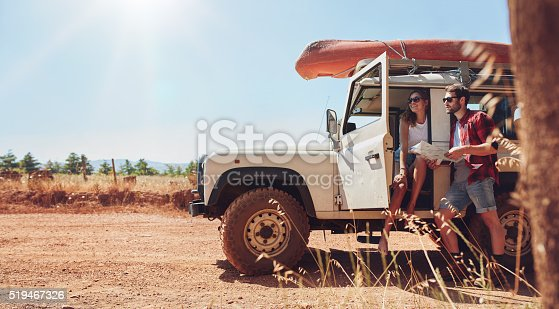 628541610istockphoto Young couple on road trip reading map for directions 519467326