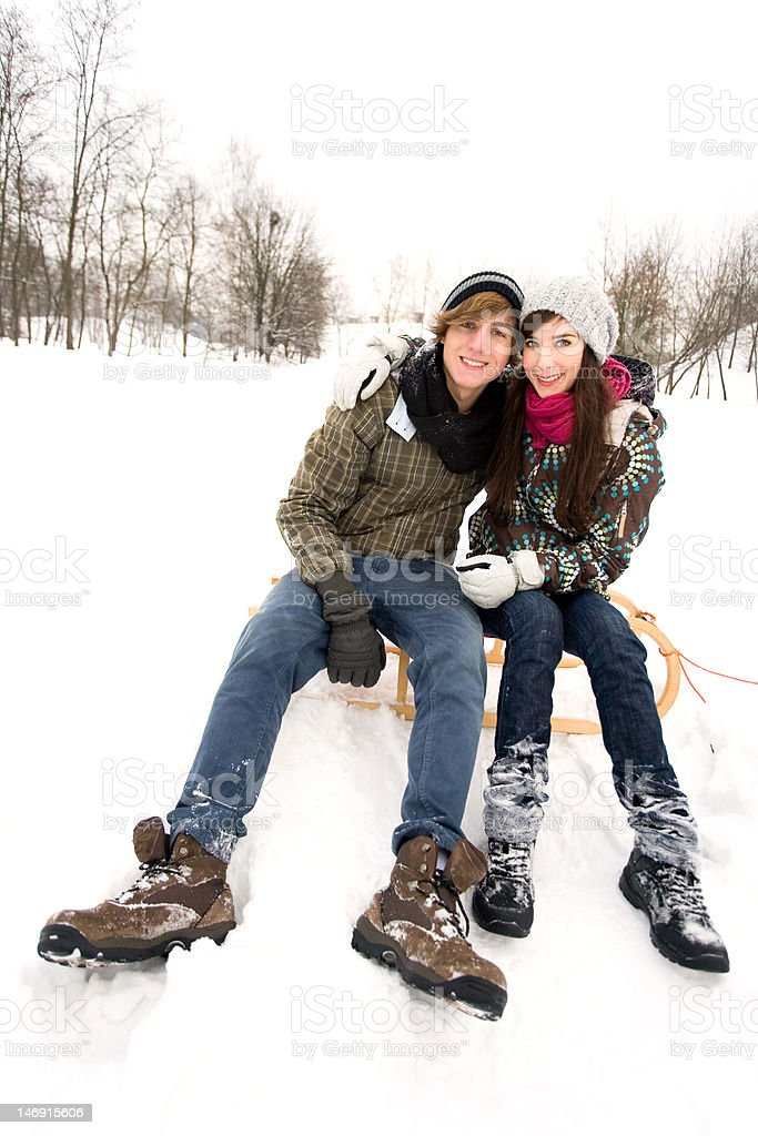 Young couple on sled in snow royalty-free stock photo