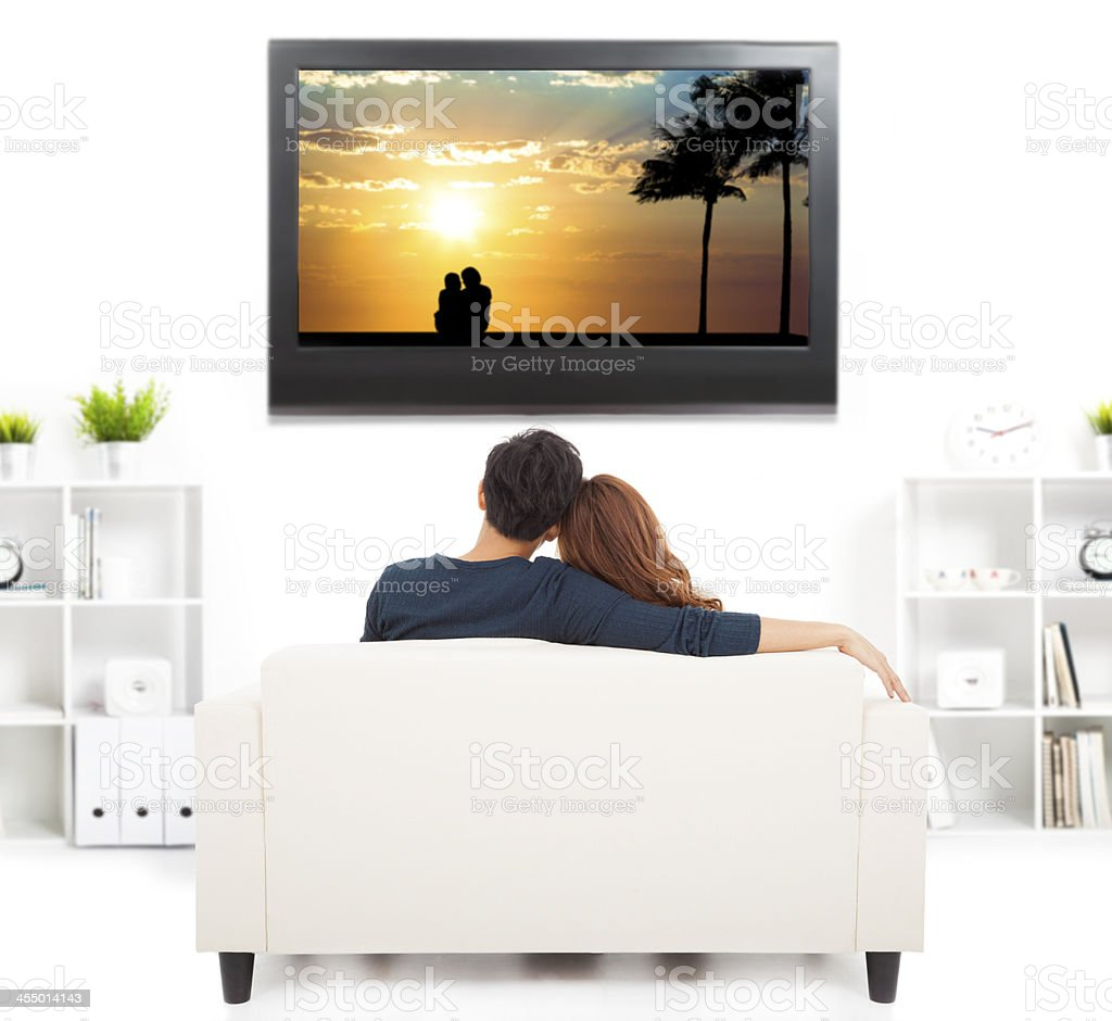 young couple on sofa watching TV stock photo