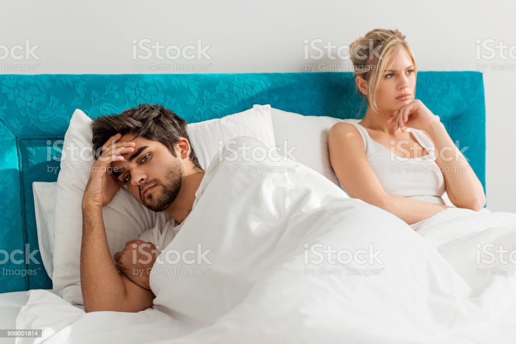 Young couple on the bed; problems in the bedroom stock photo