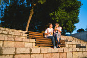Young couple sitting on the bench at sunset