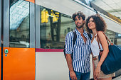 Man and woman, heterosexual couple going traveling with train together, standing on train station.