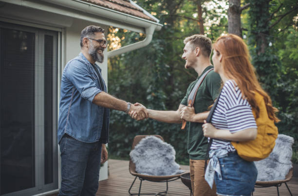 Young couple on vacation Young couple renting house. House owner shaking hands with couple who rent his house. Couple is on vacation and they are wearing backpacks. renting stock pictures, royalty-free photos & images