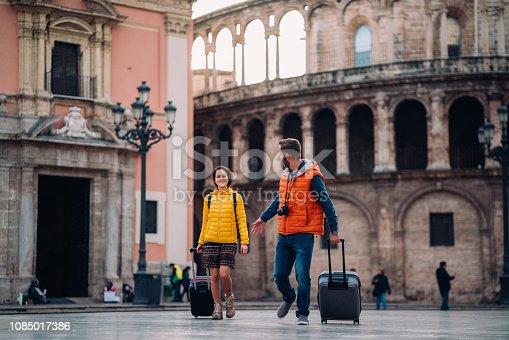Young couple with suitcases walking through Plaza de la Virgen,Valencia