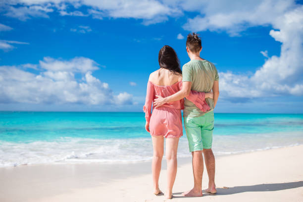 Young couple on white beach during summer vacation. Happy family enjoy their honeymoon Young couple on white beach during summer vacation. Family of two on the beach romance stock pictures, royalty-free photos & images