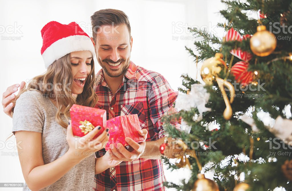 Young couple opening a Christmas present on a Christmas morning stock photo