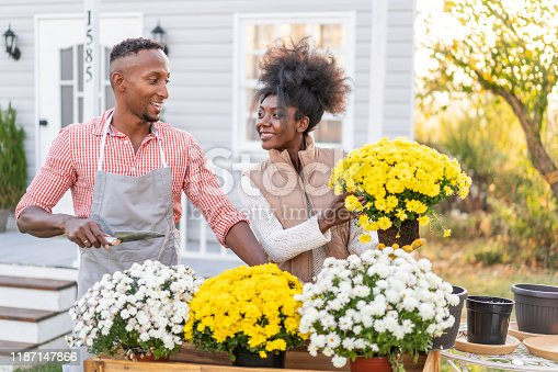Young couple outside home planting flowers  in front of a porch