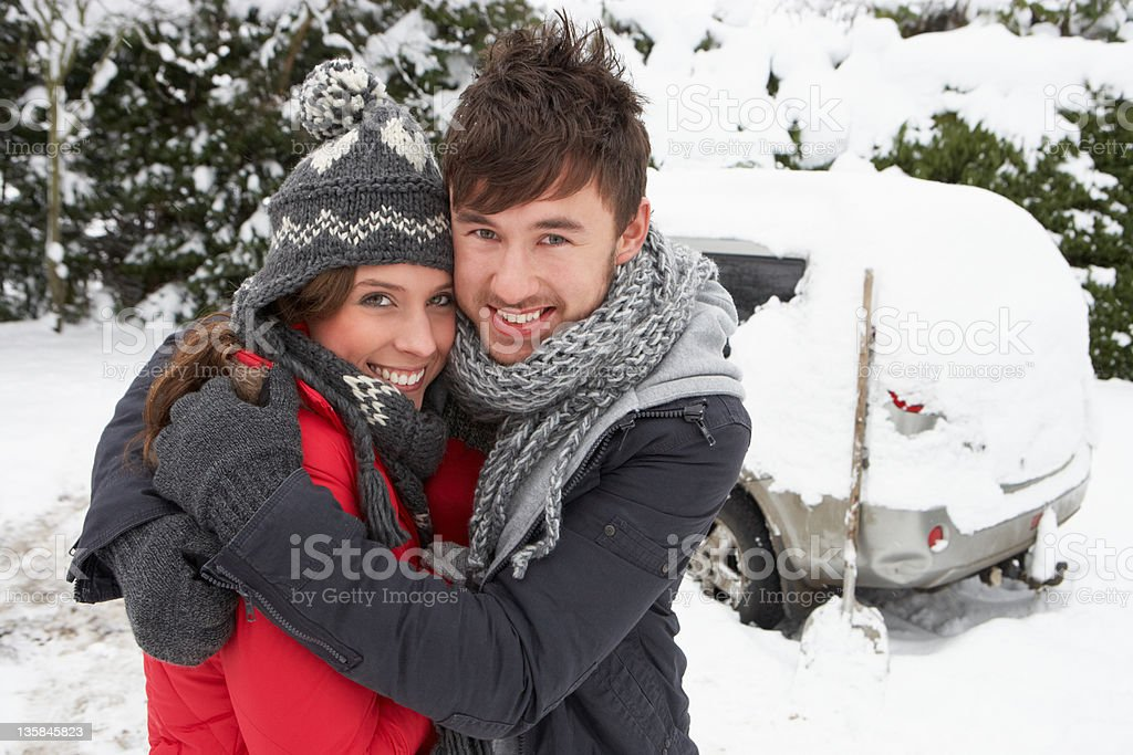 Young couple outside in the cold with car covered in snow royalty-free stock photo