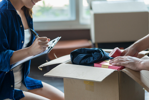 istock Young couple packing and checking stuff by using checklist before moving to new residence. 1092549906