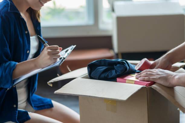 jong (echt) paar verpakking en spullen controleren met behulp van checklist voordat hij naar de nieuwe verblijfplaats. - verhuizen stockfoto's en -beelden