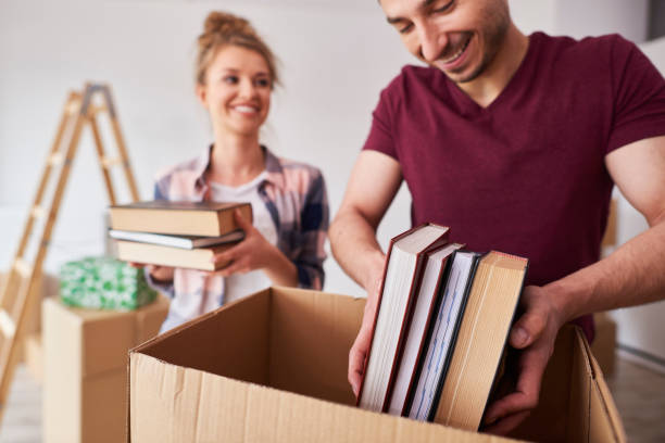 Young couple packing books into box stock photo
