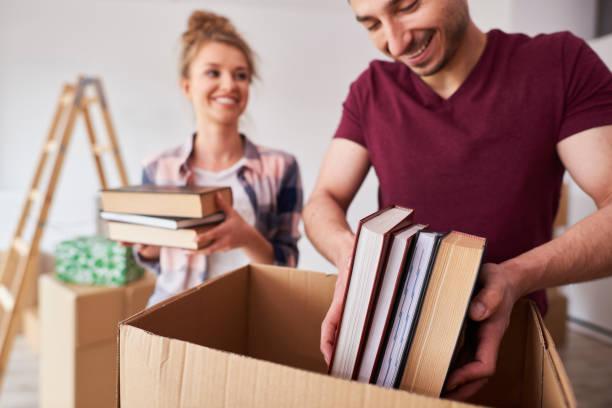 Junges Paar packt Bücher in Diebox – Foto
