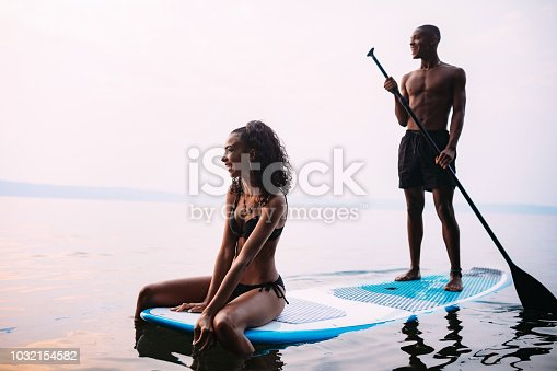 A young adult man and woman float on a standup paddleboard in the salt water of the Puget Sound, an inlet of the Pacific Ocean in Washington state, in the United States.  Rear view at sunset.  Shot at sunset.