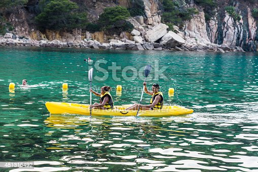 Girona, Spain - July 2, 2015: Young couple paddling in kayak on sea in Costa Brava, Catalonia