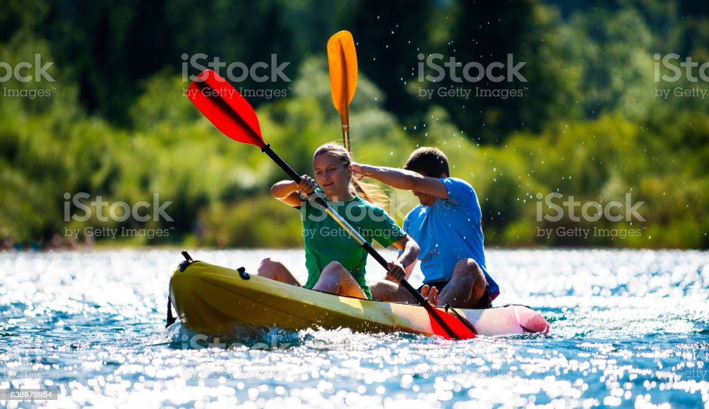 Young couple paddling in the wonder of nature in Slovenia stock photo
