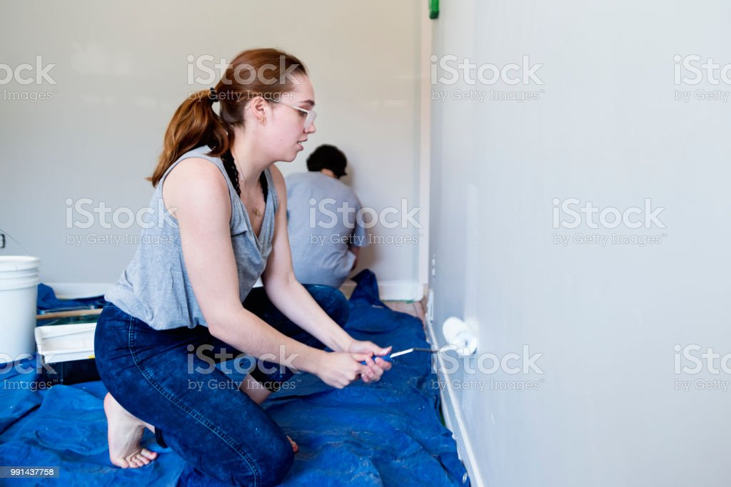 Young couple painting living room in first appartement. stock photo