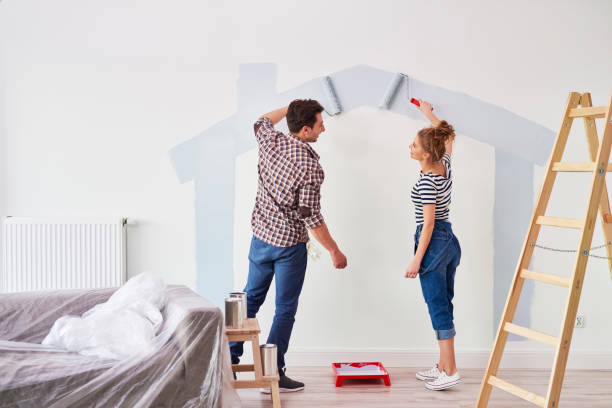 Young couple painting the interior wall in their new apartment stock photo