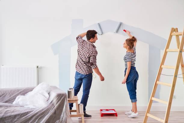 Junges Paar malt die Innenwand in ihrer neuen Wohnung – Foto