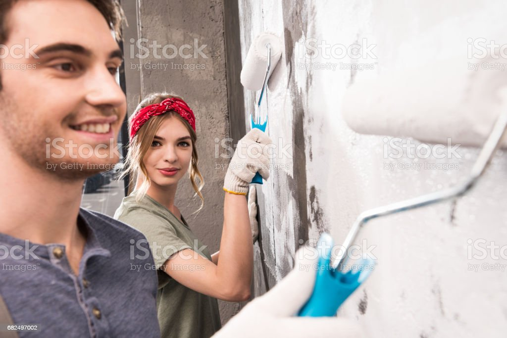 young couple painting wall together, renovation home concept foto de stock libre de derechos