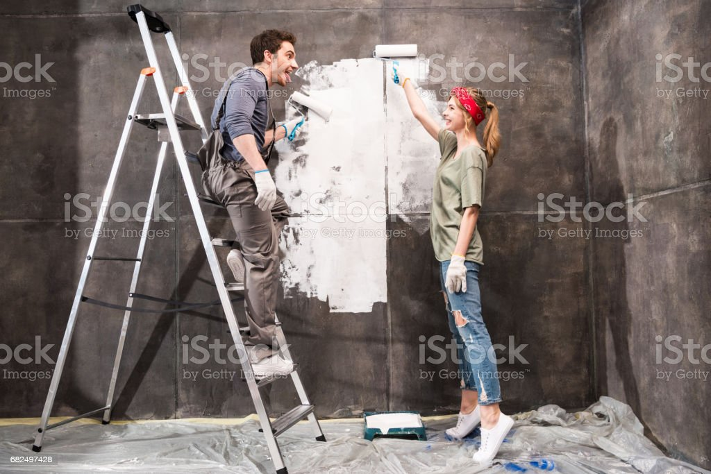 young couple painting wall together, renovation home concept royalty-free stock photo