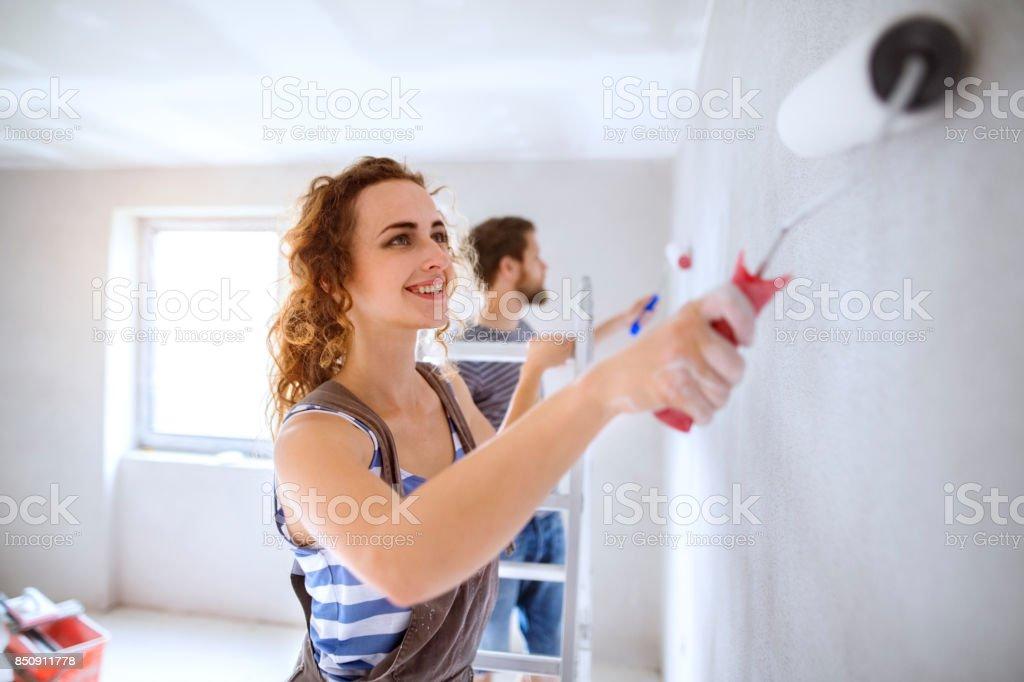 Genç çift yeni evlerinin duvarlarında resim. stok fotoğrafı