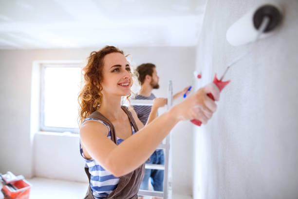 genç çift yeni evlerinin duvarlarında resim. - boya boyamak stok fotoğraflar ve resimler