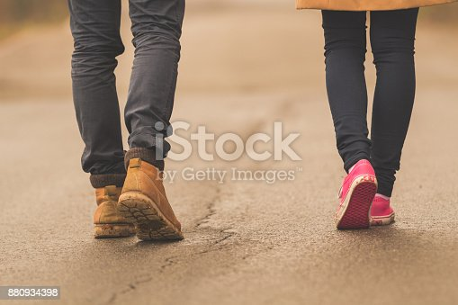 Young couple / pair walking down the street.
