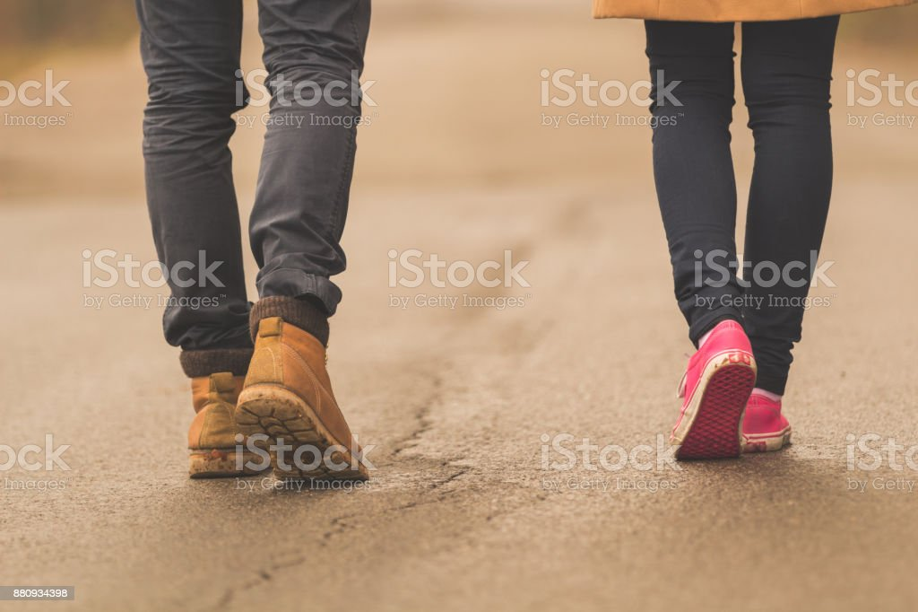 Young couple / pair walking down the street. stock photo