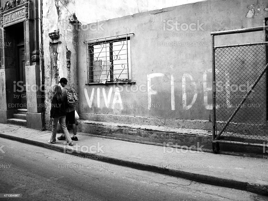 Young couple passing wall 'Viva Fidel' in old Havana stock photo