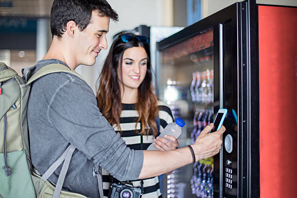 Young couple paying with mobile phone the soft drink – Foto