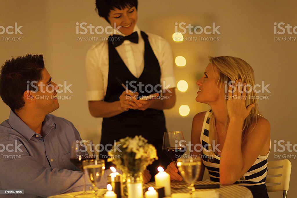 young couple place dinner order to waitress stock photo