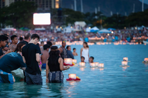 Young couple placing prayer lantern in water Honolulu, Hawaii. stock photo
