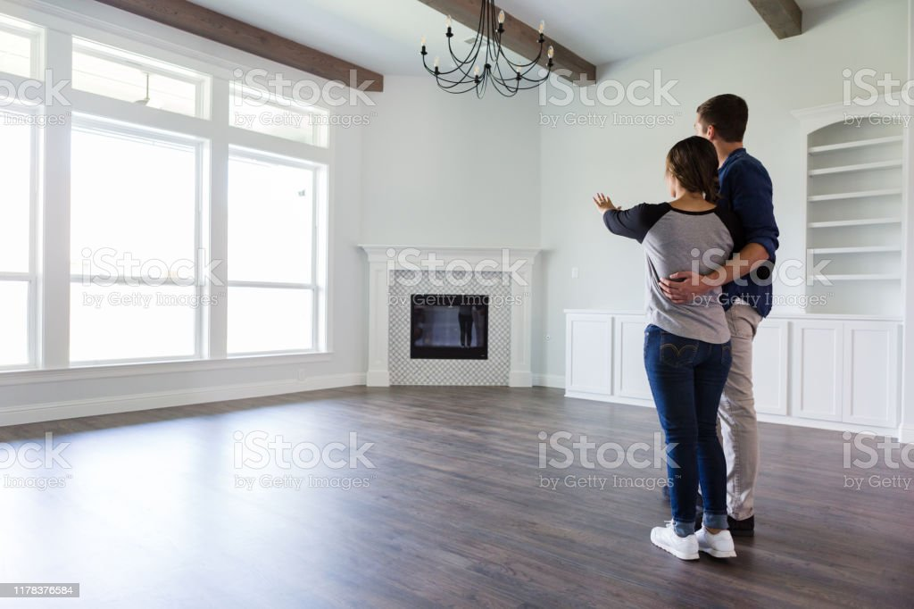 Young couple plan home decor in new home Rear view of a young couple planning the decor in the living room in their new home. Adult Stock Photo